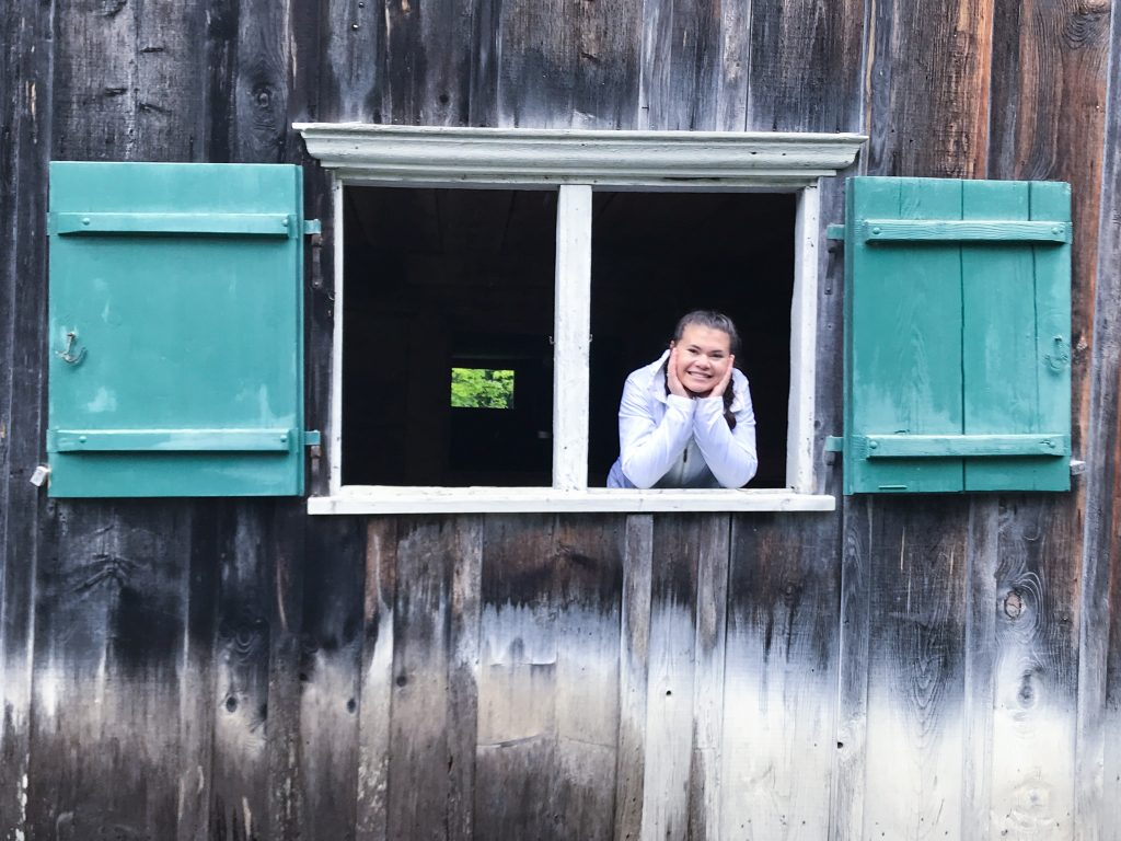 Young girl looking out window of barn
