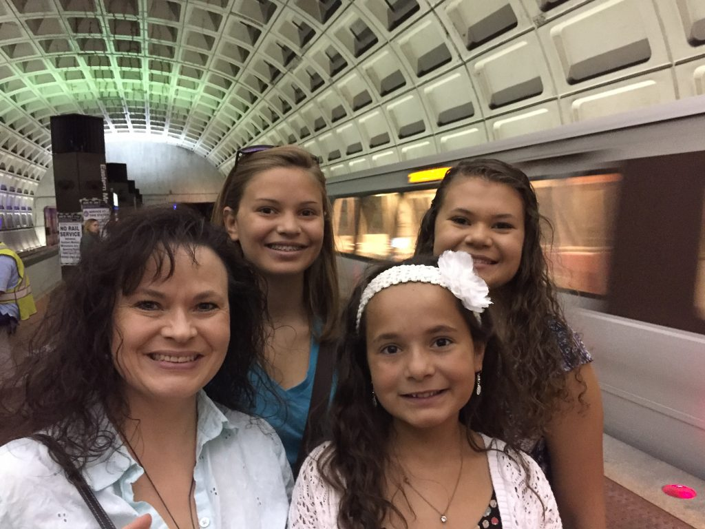 Mom with daughters on a Sunday morning taking the subway to save money
